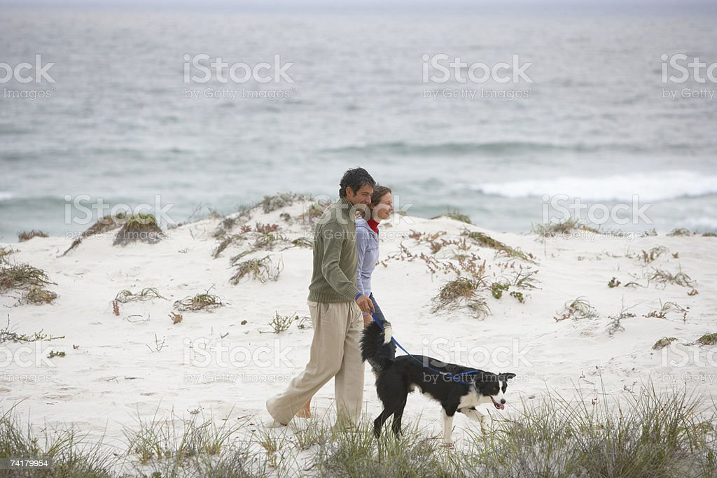 Man and woman on beach with dog royalty-free stock photo