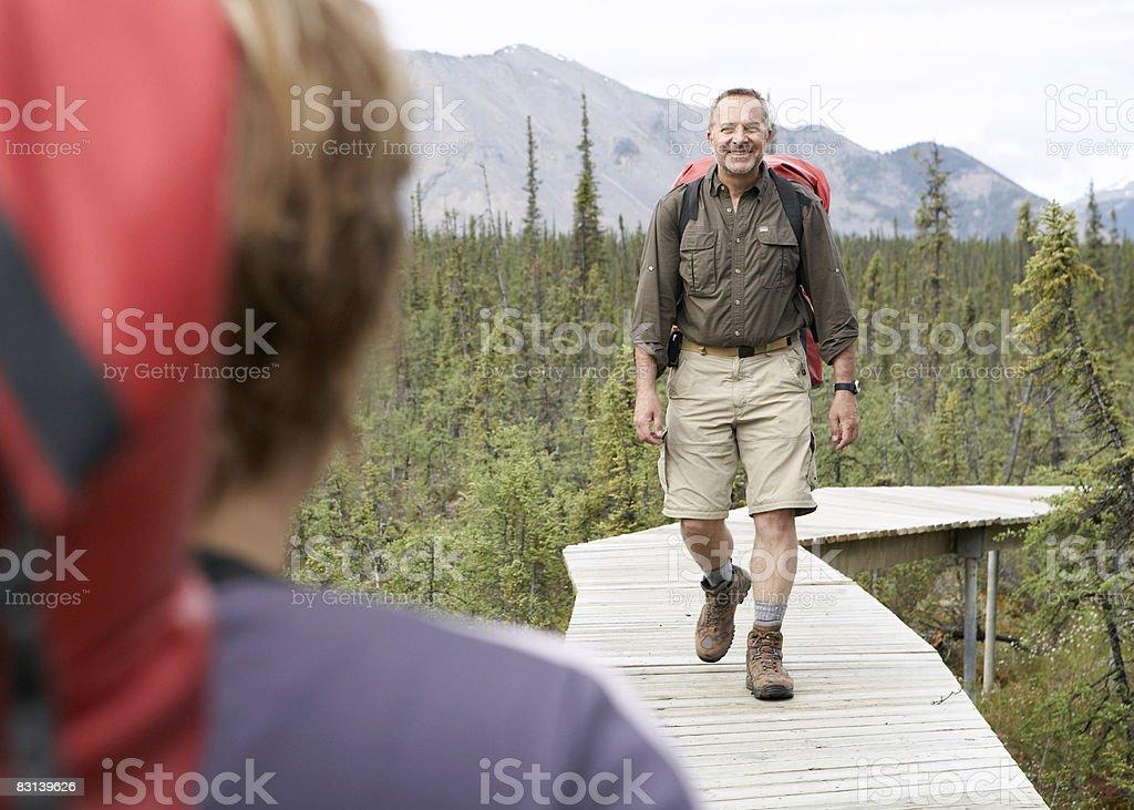 man and woman on boardwalk path in nature park zbiór zdjęć royalty-free