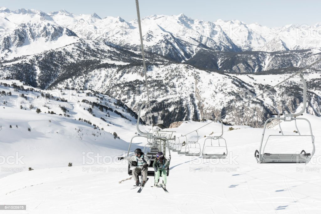 Man and woman on ski lift in Baqueira Beret Catalonia Spain stock photo