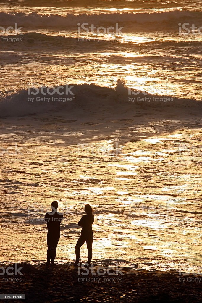 Man and woman on the beach at sunset royalty-free stock photo