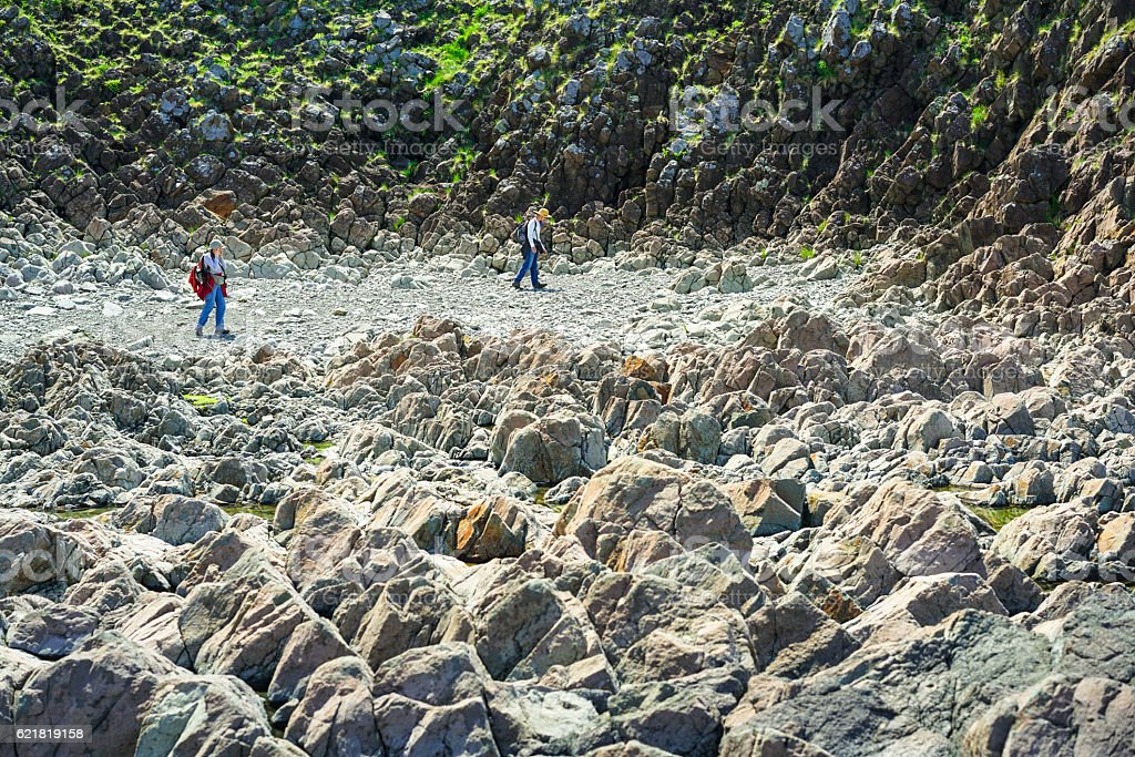 Man and woman on wild  rocky reef on Hokkaido, Japan stock photo