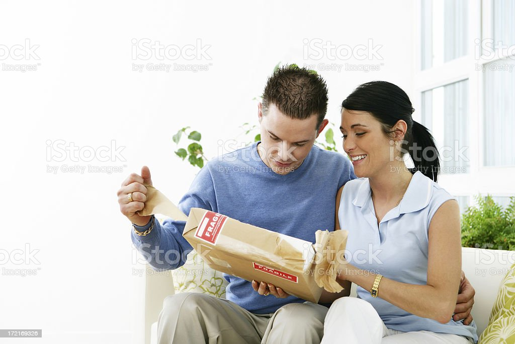 Man and woman opening a parcel royalty-free stock photo