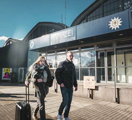 Man and woman passing by Police station in Germany