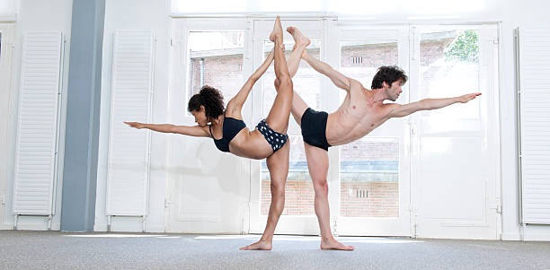 man and woman performing standing bow pulling pose stock photo