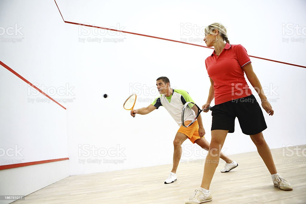 Man and woman play singles game of squash stock photo