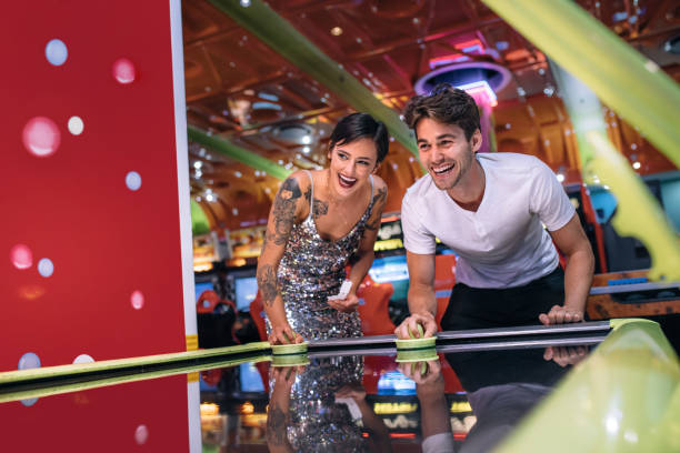 Man and woman playing air hockey game at a gaming parlour stock photo