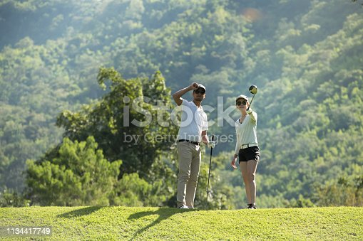 istock Man and woman playing golf on a beautiful natural golf course 1134417749