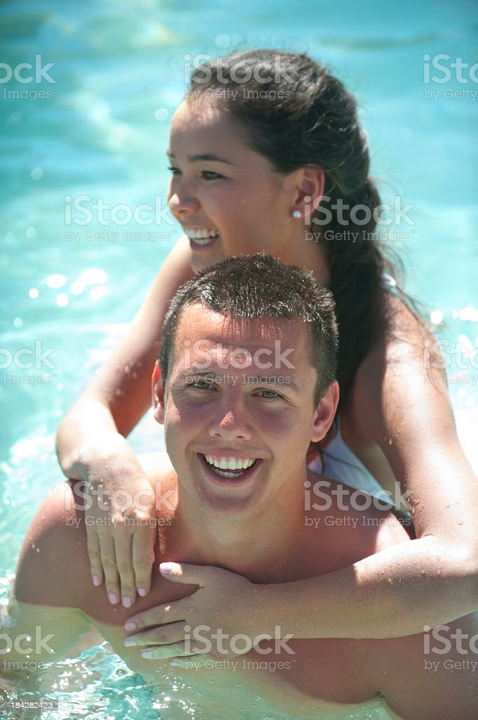 Man and woman playing in a swimming pool royalty-free stock photo