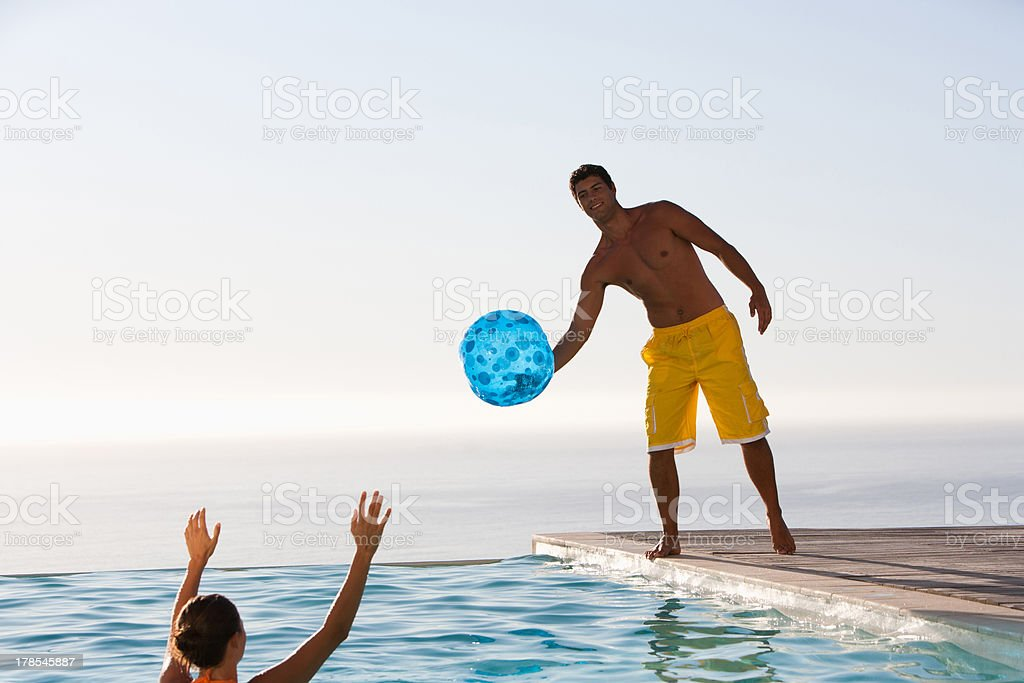 Man and woman playing with ball in swimming pool stock photo