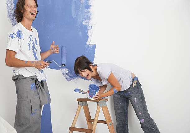 Man and woman playing with paint stock photo
