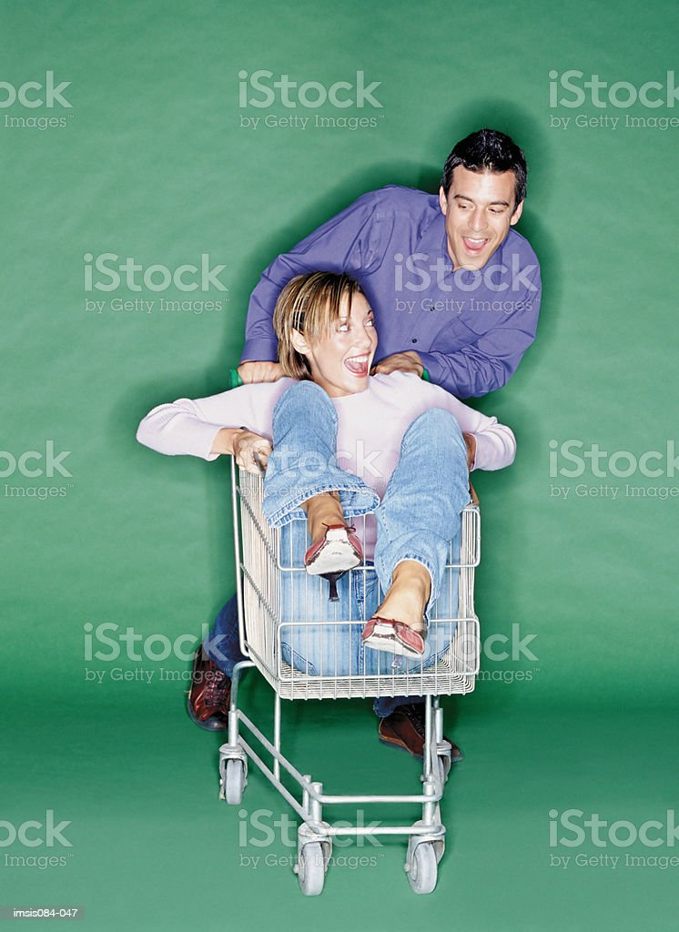 Man and woman playing with shopping trolley royalty-free stock photo
