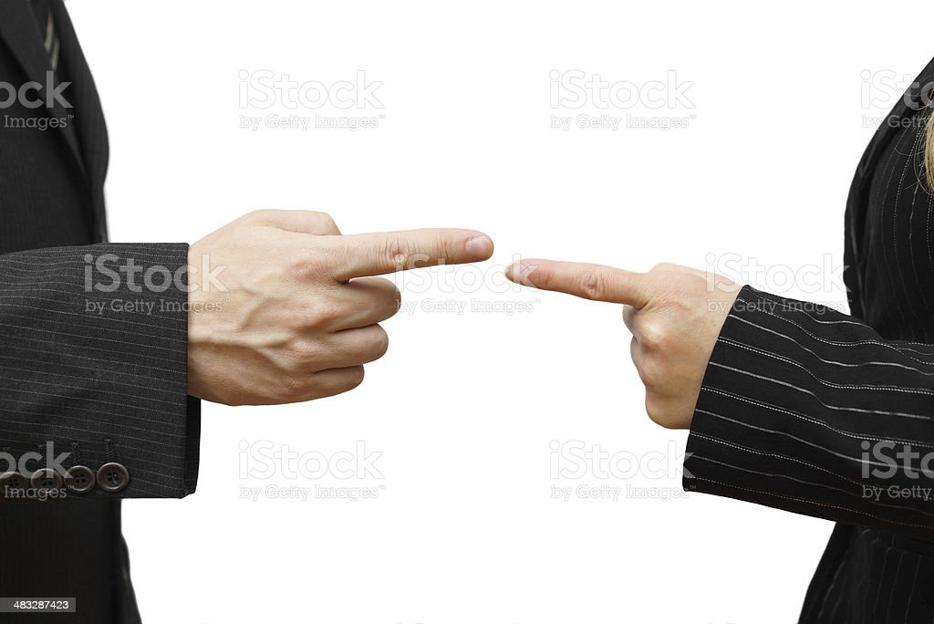 man and woman pointing against each other stock photo