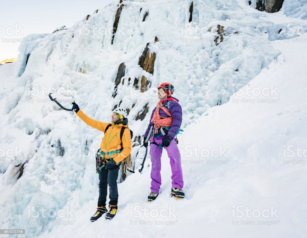 Man and woman preparing for ice climbing day stock photo