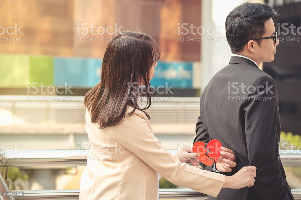 Man And Woman Pulling A Red Paper Heart Apart The Concept Of