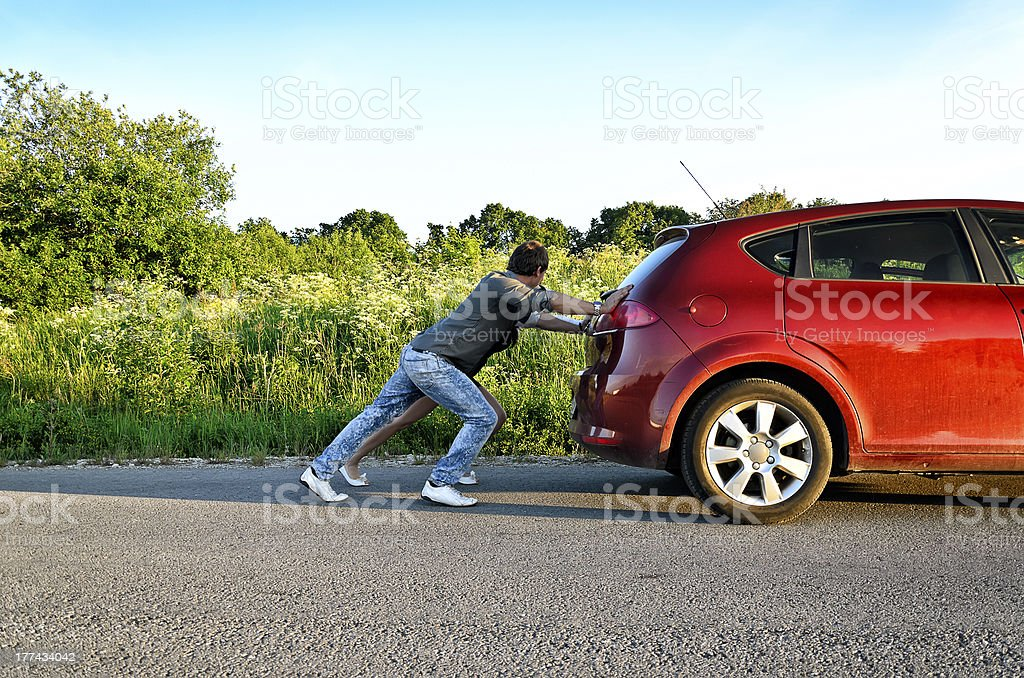 Man and woman pushing a broken car stock photo