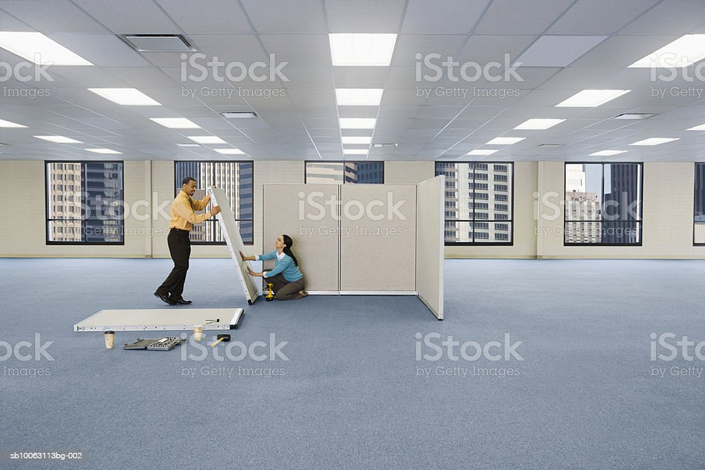Man and woman putting cubicle together royalty-free stock photo