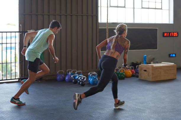 mann und frau rennen einander beim fitness-training in der turnhalle - laufende tattoos stock-fotos und bilder