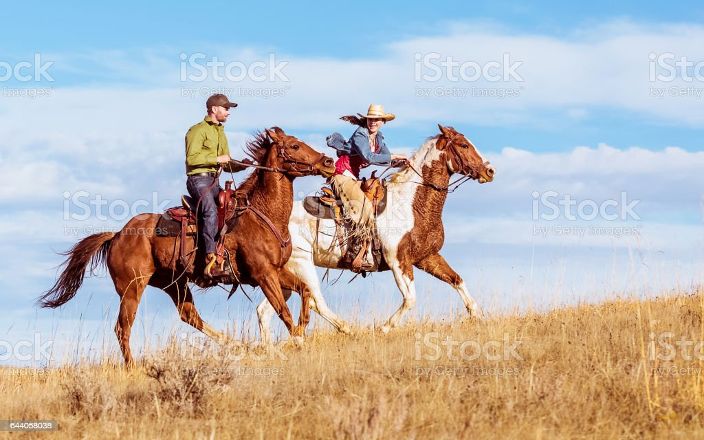 Man And Woman Racing Up Grassy Hill On Horseback stock photo