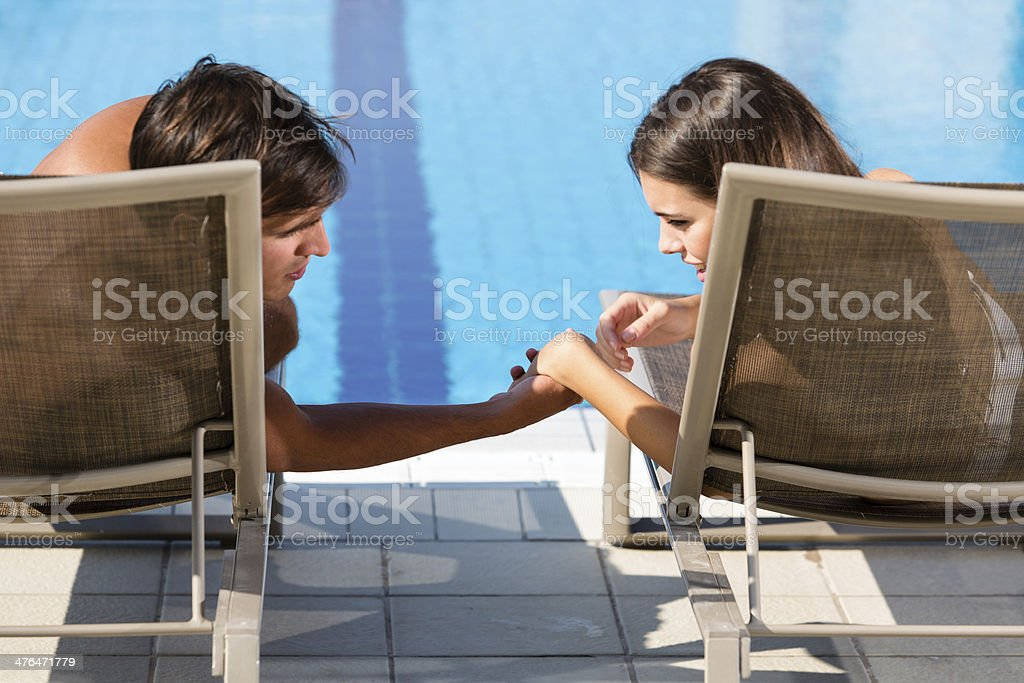 Man and woman relaxing by the swimming pool royalty-free stock photo
