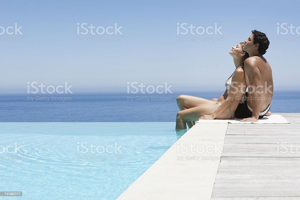 Homem e mulher relaxante no Lago Infinito pavimento em swimsuits foto de stock royalty-free