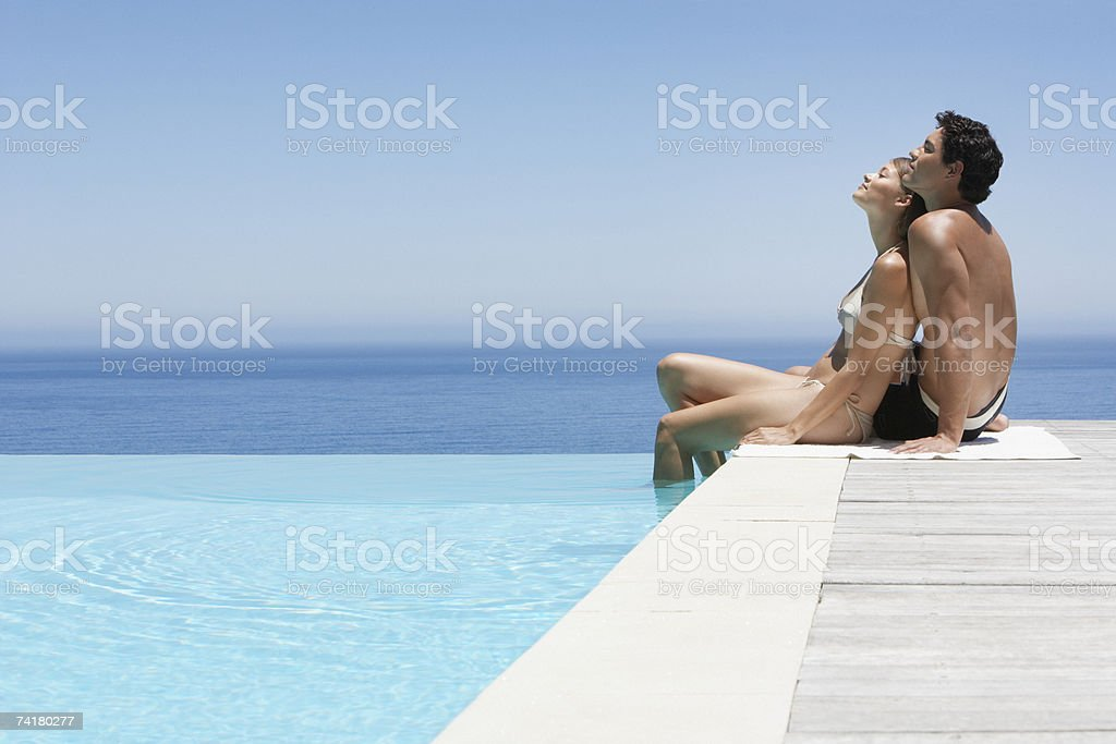 Man and woman relaxing on infinity pool deck in swimsuits stock photo