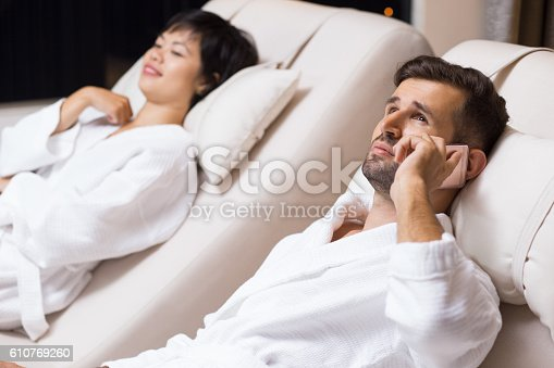 610769340istockphoto Man and Woman Relaxing on Loungers in Spa Salon 610769260