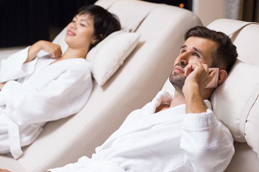 610769340 istock photo Man and Woman Relaxing on Loungers in Spa Salon 610769260