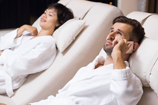 man and woman relaxing on loungers in spa salon - call center stockfoto's en -beelden