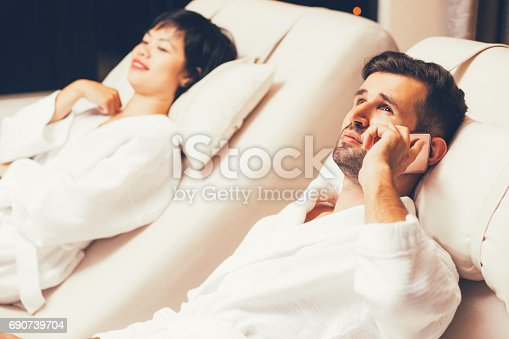 610769340istockphoto Man and Woman Relaxing on Loungers in Spa Salon 690739704