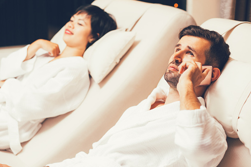 610769340 istock photo Man and Woman Relaxing on Loungers in Spa Salon 690739704
