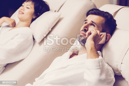 610769340istockphoto Man and Woman Relaxing on Loungers in Spa Salon 953553286