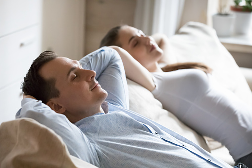 973962076 istock photo Man and woman relaxing on soft comfortable sofa at home 1155911389