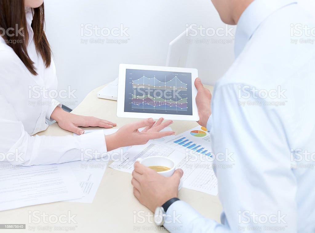 Man and woman reviewing finances with tablet royalty-free stock photo