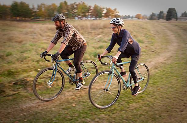 Man and woman riding their bikes through a field stock photo