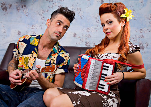 Man and Woman Rockabilly Couple Sitting on Couch Playing Instruments stock photo