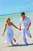 fc54a91a777e Man and woman romantic couple in white clothes holding hands running in the  sea water on