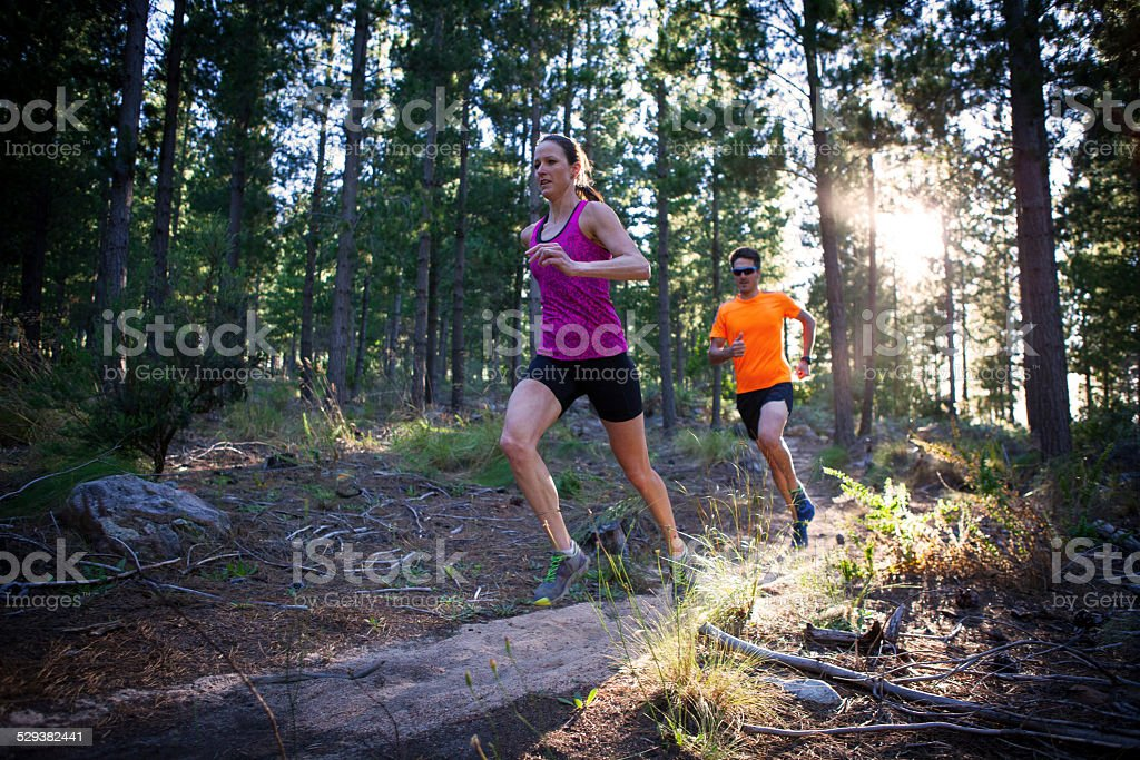 Man and woman running in the forest early morning stock photo