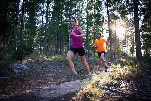 hombre y mujer corriendo en el bosque por la mañana - trail running fotografías e imágenes de stock