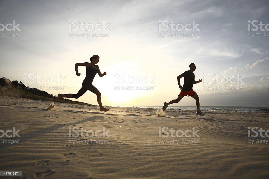 Mann und Frau Laufen am Strand bei Sonnenuntergang - Lizenzfrei Aktiver Lebensstil Stock-Foto