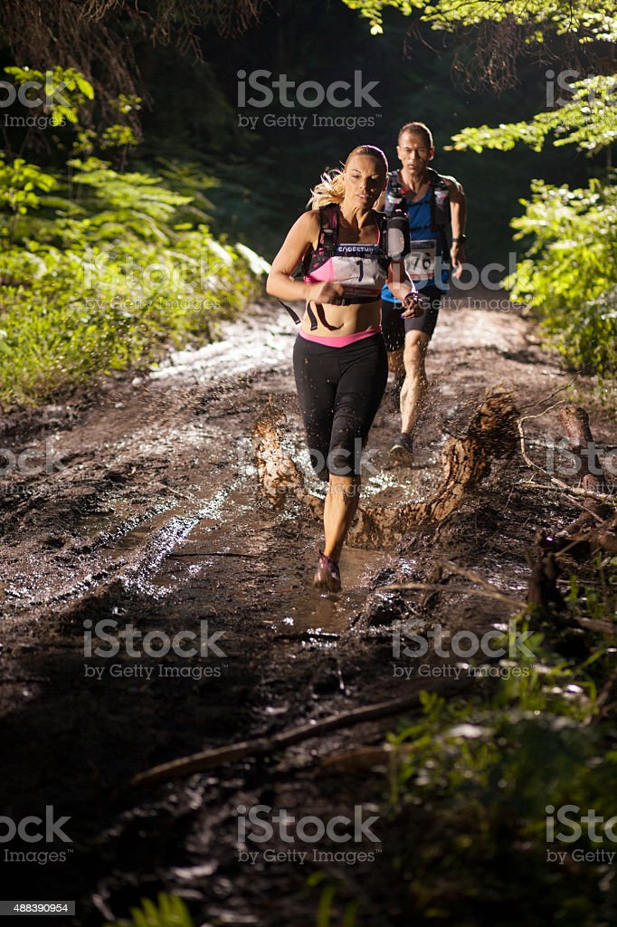 Man and woman running through dirt track in ultramarathon race stock photo
