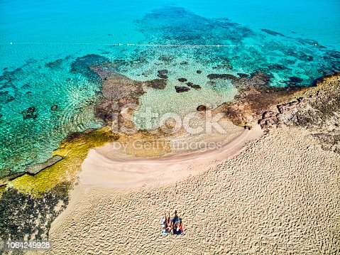 Couple seated in sand at Cala Conta, a clear water and beaultiful beach in the island of Ibiza - Spain