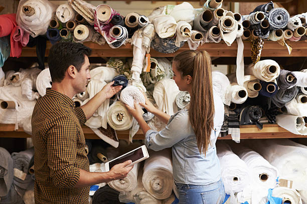 man and woman selecting fabric from storage shelves - textilindustrie stock-fotos und bilder