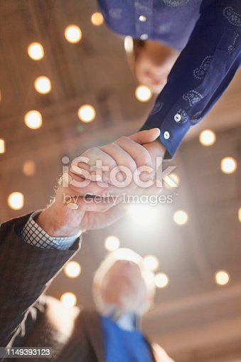 istock Man and woman shaking hands in design office 1149393123