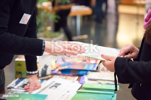 Man and Woman Sharing Information Leaflet over Exhibition Stand