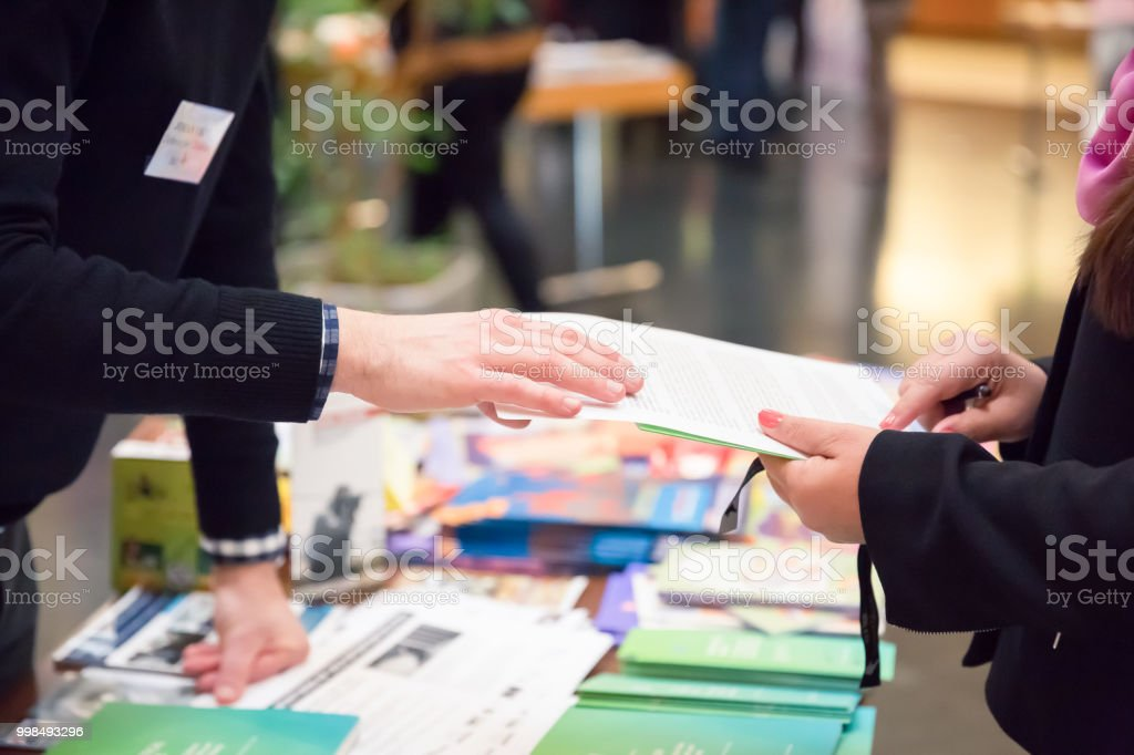 Man and Woman Sharing Information Leaflet over Exhibition Stand stock photo