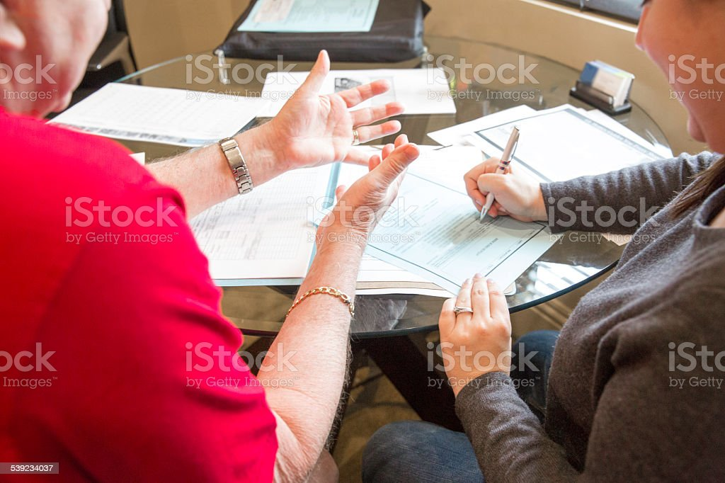 Man and woman signing documents on glass table royalty-free stock photo
