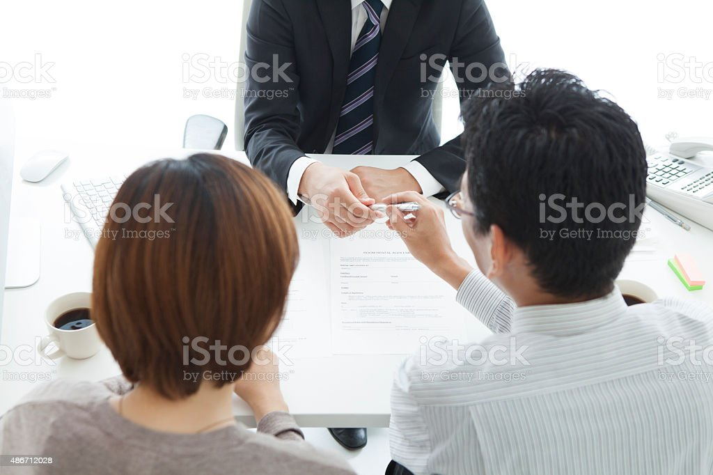 Man and woman signing loan contract stock photo