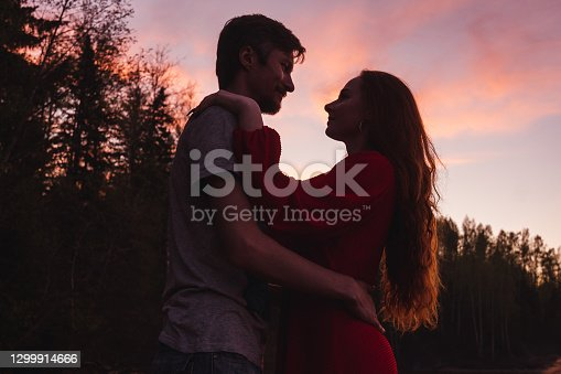 Man and woman silhouettes on pink sunset sky background. Valentine day concept.