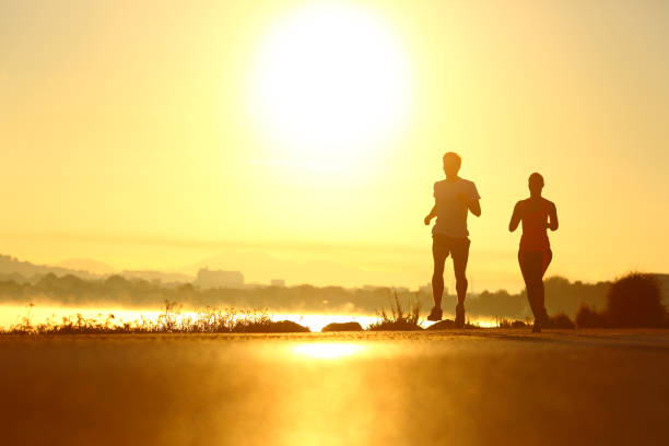 Man and woman silhouettes running at sunrise stock photo
