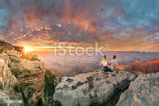 istock Man and woman sit on the edge of rim talking about future and watching the Grand Canyon sunset 1143601788